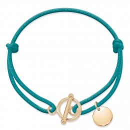 Bracelet avec fermoir rond plaqué or et pendentif médaillon plaqué or sur un cordon épais bleu turquoise.